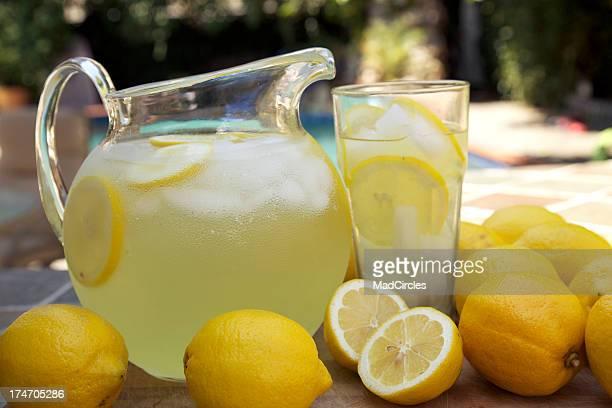 Round glass jug of fresh lemonade with sliced lemons at pool