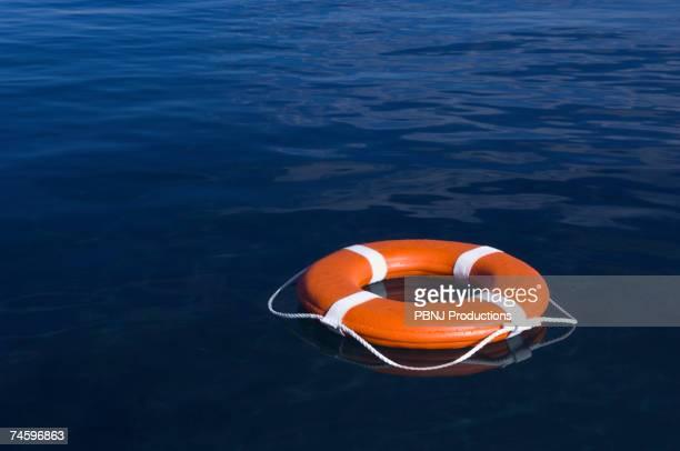 round life preserver floating in water - betrouwbaar stockfoto's en -beelden