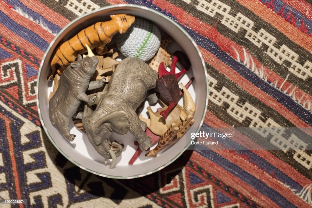 A round metal box with toys inside on a carpeted floor : Foto de stock
