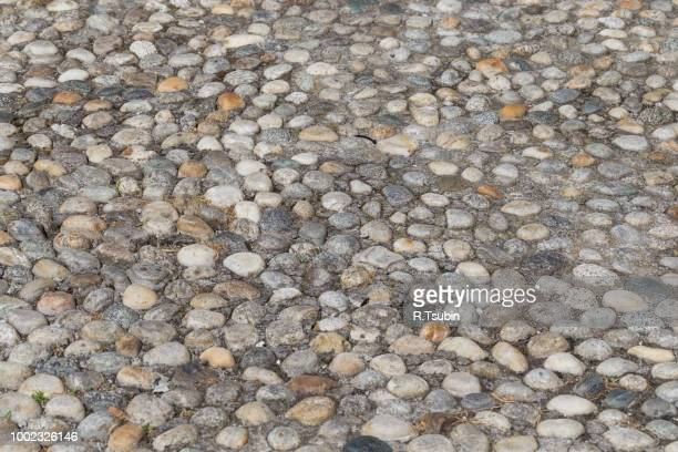 Round stones in the ground. Texture of the cobblestones in Park. Paved road for pedestrians. The paving stones. Background
