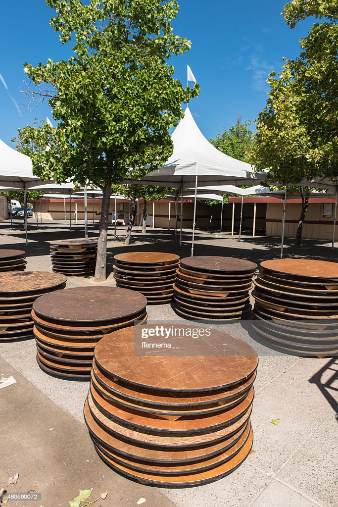Round tables stacked outdoors by tent : Stock Photo