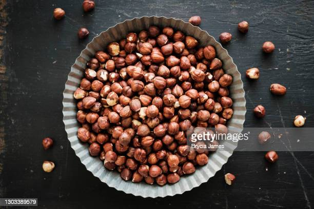 round tin of shelled hazelnuts on black - brycia james stock pictures, royalty-free photos & images