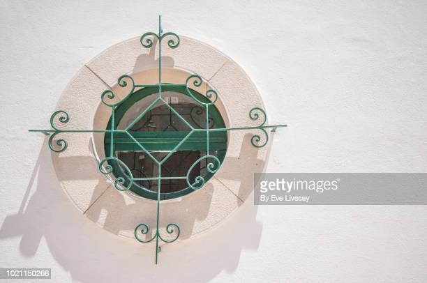 round window in faro old town - faro city portugal stock photos and pictures
