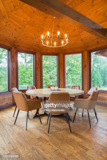 round wooden dining table with tan leather armchairs in dining room inside milled eastern white pine timber and flat log profile home, quebec, canada - eastern white pine stock pictures, royalty-free photos & images