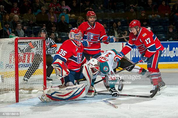 Rourke Chartier of the Kelowna Rockets is checked to the ice by Jeremy McIntosh and Mitch Holmberg in front of the net of Eric Williams of the...