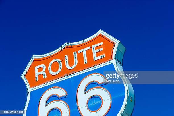 Route 66 sign against blue sky, low angle view