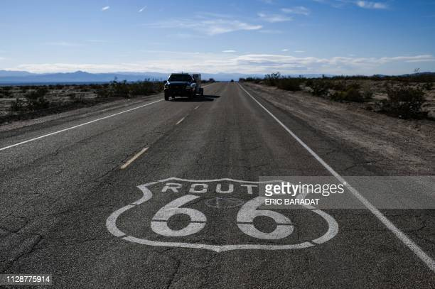 A Route 66 sign is painted on the asphalt near Amboy in the Mojave Desert in California on February 27 2019 USRoute 66 also known as the Will Rogers...