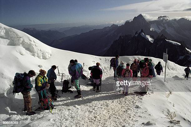 Route to the Mont Blanc A group of mountaineer cover a distance between Aiguille du Midi and the Mont Blanc France Alps