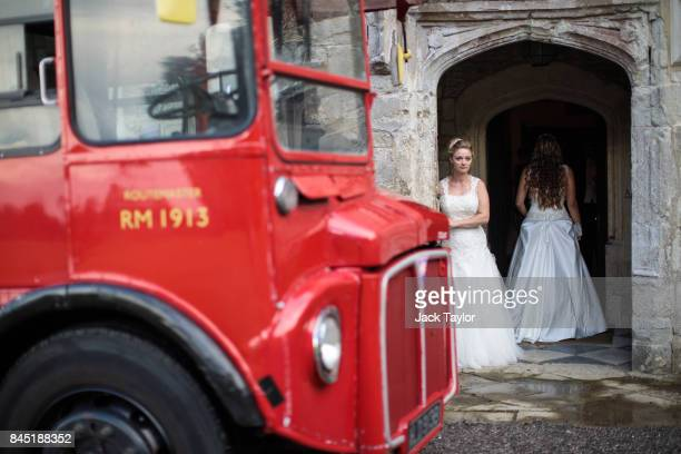 Routemaster bus is parked outside as debutante Lauren Evans from Haslemere looks out of the entrance to Boughton Monchelsea Place ahead of the Queen...