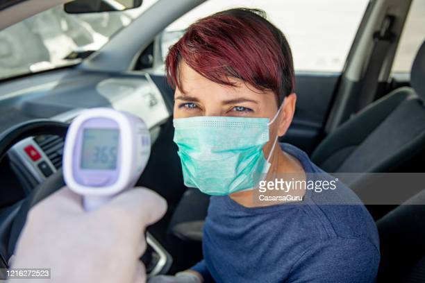 routine testing for body fever on population during covid-19 crisis - infrared thermometer stock pictures, royalty-free photos & images