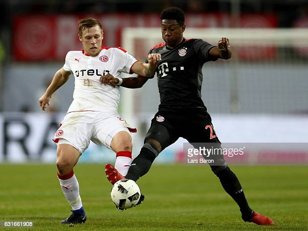 Rouwen Hennings of Duesseldorf is challenged by David Alaba of Bayern Muenchen during the Telekom Cup 2017 match between Fortuna Duesseldorf and...