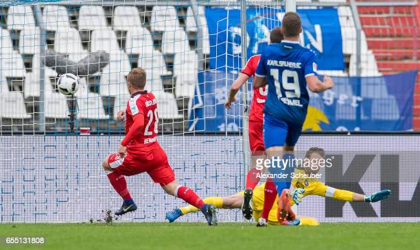 Rouwen Hennings of Fortuna Duesseldorf scores the first goal for his team against Dirk Orlishausen of Karlsruhe during the Second Bundesliga match...