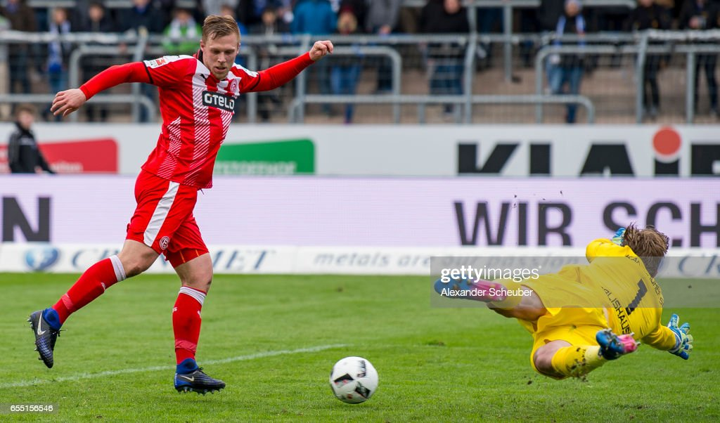 Rouwen Hennings of Fortuna Duesseldorf scores the third goal for his team against Dirk Orlishausen of Karlsruhe during the Second Bundesliga match between Karlsruher SC and Fortuna Duesseldorf at Wildparkstadion on March 19, 2017 in Karlsruhe, Germany.