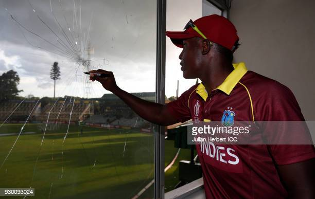 Rovman Powell of The West Indies signs a window he broke in the press room whilst batting during The ICC Cricket World Cup Qualifier between The West...