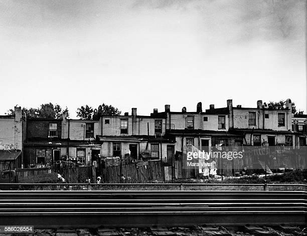 Row houses in disrepair line railroad tracks through a slum of Baltimore Maryland USA