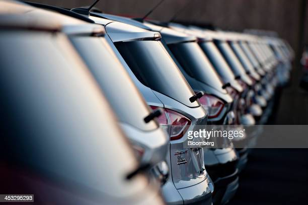 A row of 2014 Ford Motor Co Escape vehicles sit on display at Uftring Ford in East Peoria Illinois US on Saturday Nov 30 2013 Automakers entered...