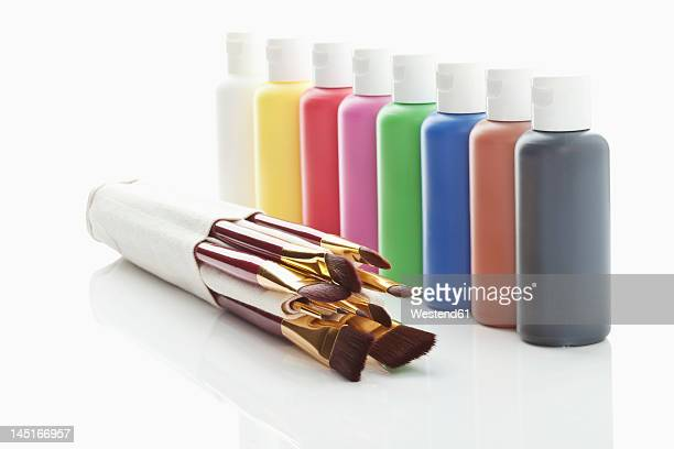 Row of acrylic color bottles and paint brushes on white background