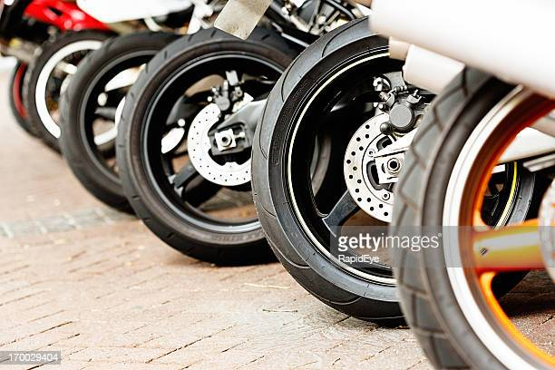 Row of assorted motorbike wheels on brick surface