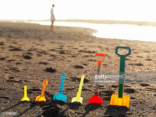 Row of assorted plastic spades standing in sand