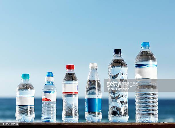 Row of assorted water bottles against the ocean