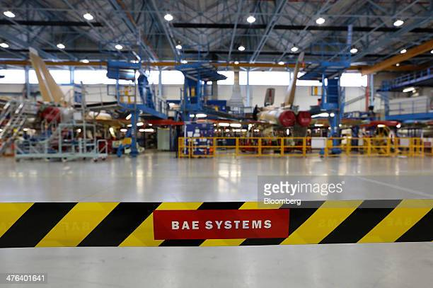 A row of BAE Eurofighter Typhoon jets are seen beyond a security tape in the final assembly hangar at the BAE Systems Plc plant in Warton UK on...