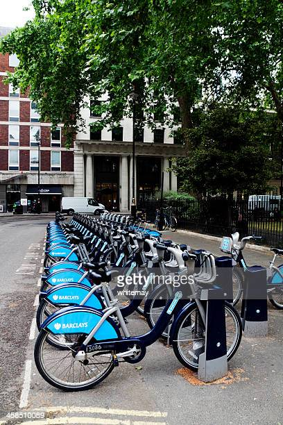 row of barclays bikes in a london square - barclays cycle hire stock pictures, royalty-free photos & images