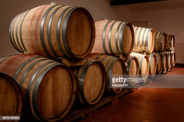 row of barrels emerging from darkness in a wine cellar - バーボンウイスキー ストックフォトと画像