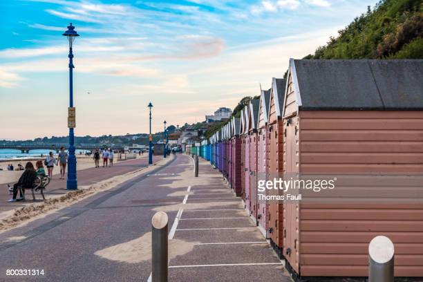 row of beach huts on bournemouth beach - bournemouth england stock photos and pictures