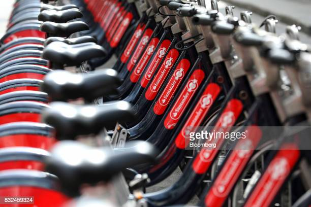 A row of bicycles available to hire stand in the street with logos of sponsor Banco Santander SA in London UK on Tuesday Aug 15 2017 Banco Santander...