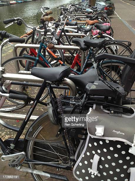 CONTENT] A row of bicycles stretches along a canal in Amsterdam