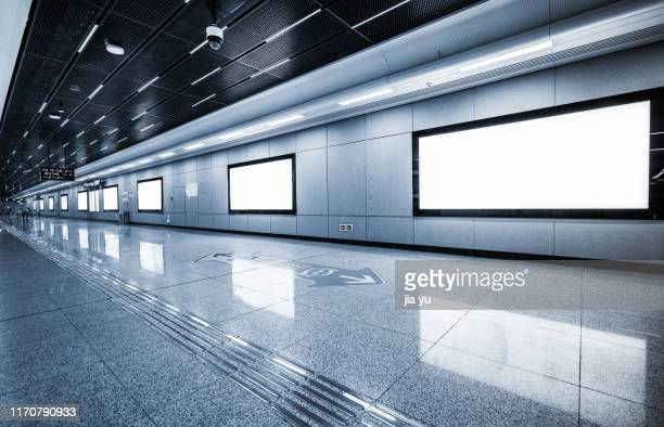 row of blank billboards on wall in subway station - subway station stock pictures, royalty-free photos & images