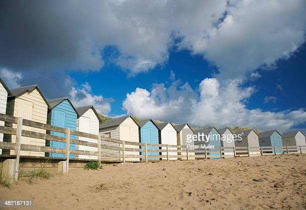 A row of blue and white beach huts, Bude, Cornwall, UK