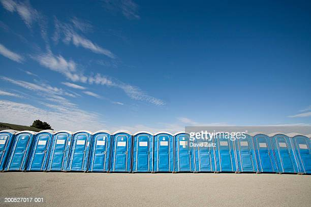 Row of blue plastic portable toilets against blue sky, low angle view