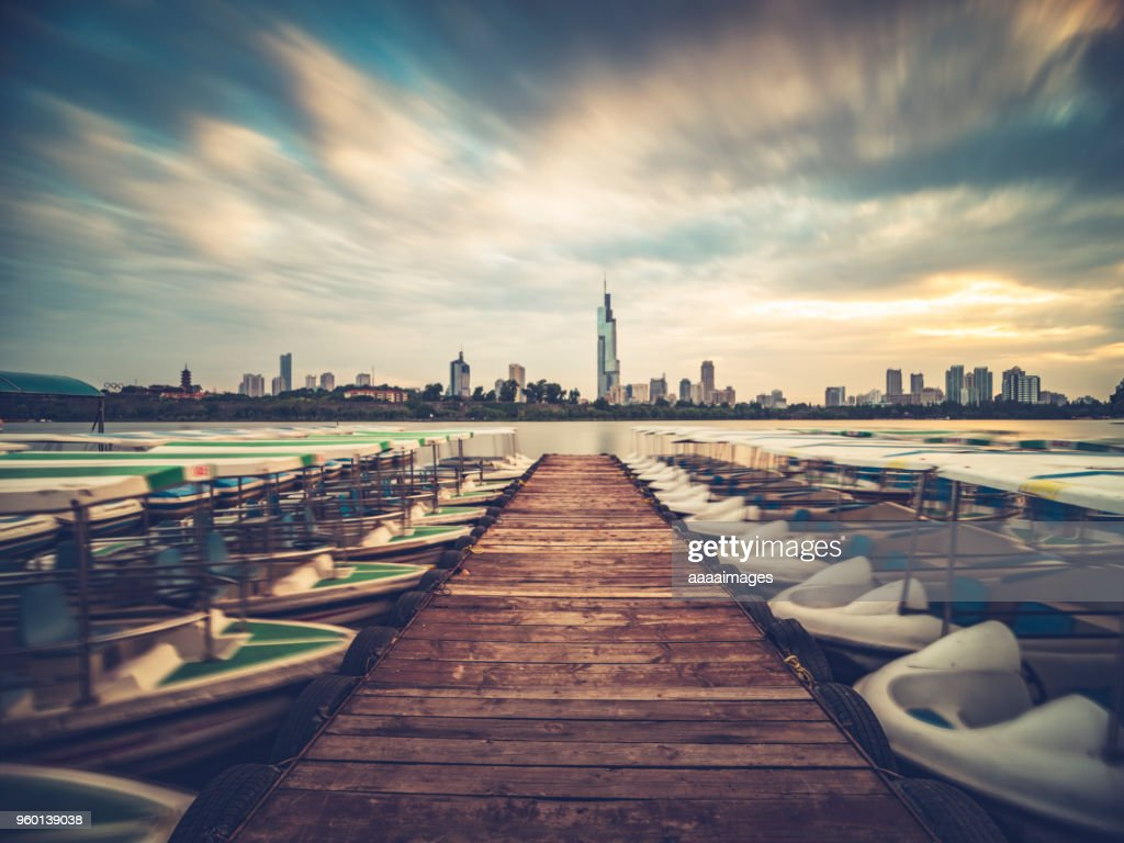 row of boats moored at xuanwu lakeside with the Zifeng Tower on background : Stock-Foto