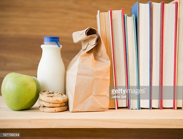 Row of books and lunch bag on shelf
