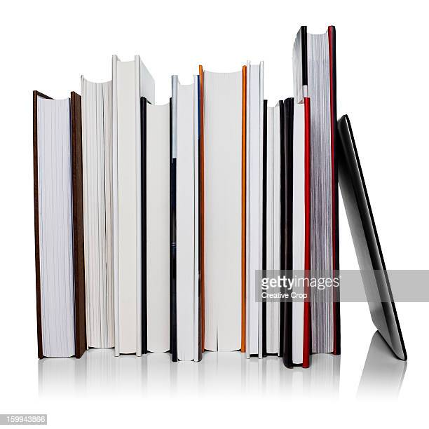 Row of books leaning against a tablet computer