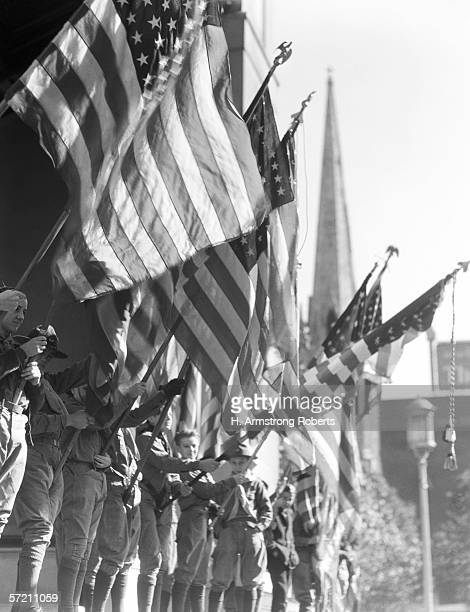 Row of boy scouts in uniform holding American flags