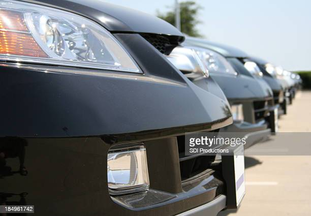 row of brand newblack sedans parked at a car lot - bumper stock pictures, royalty-free photos & images