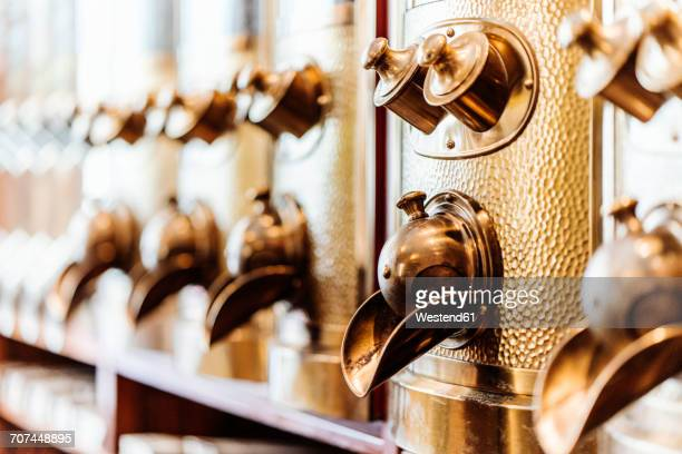 Row of brass coffee dispensers