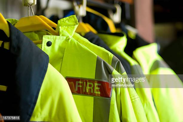 a row of british firefighter jackets neatly hung up for use - fire station stock photos and pictures