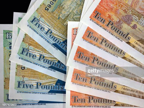 A row of British five and 10pound banknotes sit in this arranged photograph in London UK on Wednesday Aug 15 2018 The pound's weakness is turning...