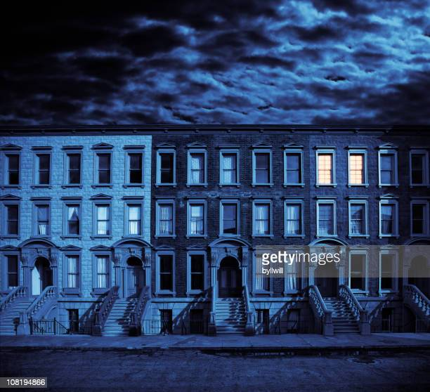row of brownstone houses against cloudy night sky - brownstone stock pictures, royalty-free photos & images
