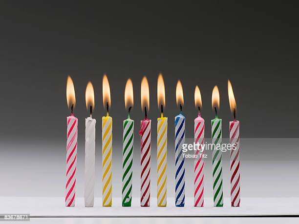 A row of burning multi colored birthday candles