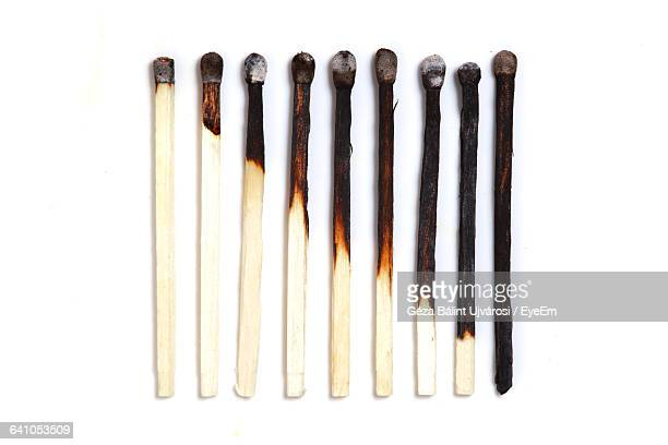 row of burnt matchsticks against white background - fiammifero foto e immagini stock