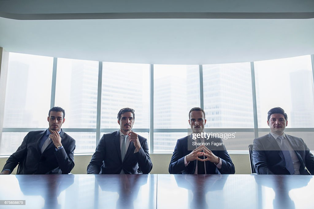 Row of businessmen sitting at conference table : Stock Photo