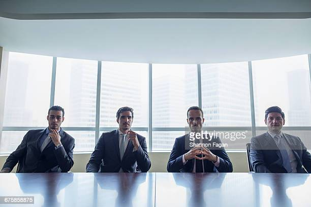 Row of businessmen sitting at conference table