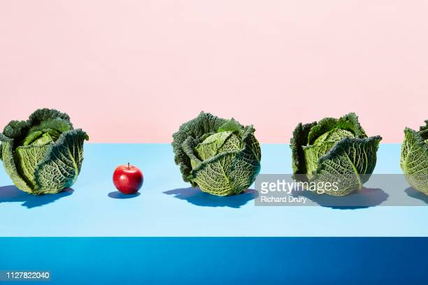 a row of cabbages with one red apple - richard drury stock pictures, royalty-free photos & images