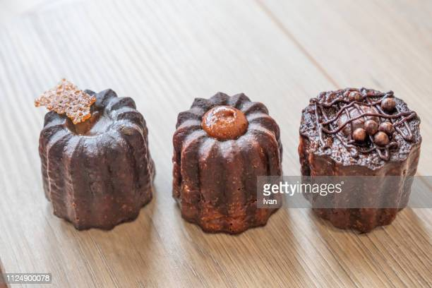 A row of caneles with various flavor, original, chocolate, and caramel.