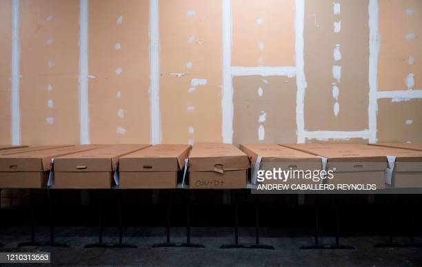 A row of cardboard caskets one reading COVID containing the bodies of deceased are laid across a table before being cremated at Maryland Cremation...