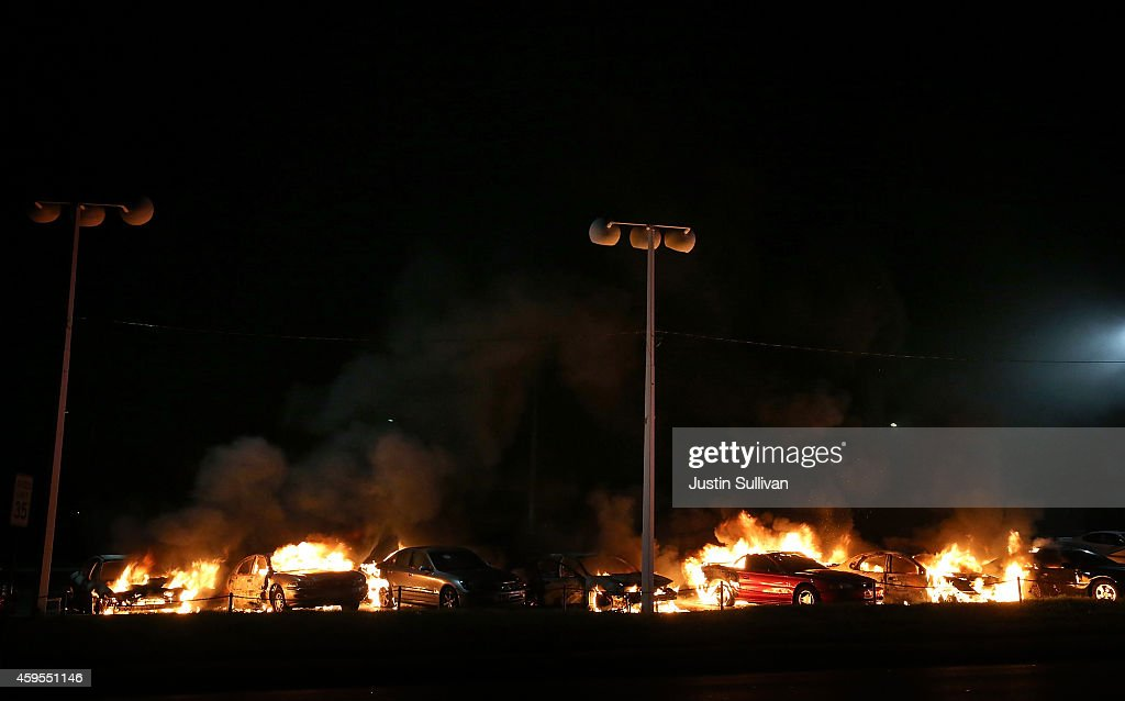 A row of cars burn at a used car lot during a demonstration on November 25, 2014 in Ferguson, Missouri. Ferguson has been struggling to return to normal after Brown, an 18-year-old black man, was killed by Darren Wilson, a white Ferguson police officer, on August 9. His death has sparked months of sometimes violent protests in Ferguson. A grand jury today declined to indict officer Wilson.